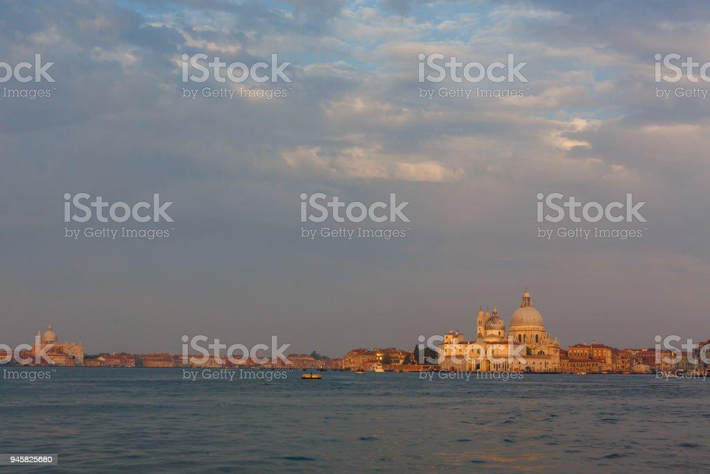 Basilica di Santa Maria della Salute at orange colors reflected on the water surface, Venice, Italy. stock photo
