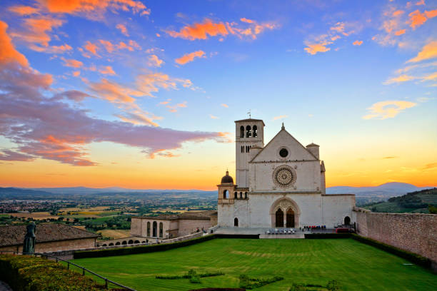 Basilica of San Francis of Assisi at sunset under beautiful orange and blue skies, Italy Basilica of San Francis of Assisi at sunset under beautiful glowing orange and blue skies, Italy umbria stock pictures, royalty-free photos & images