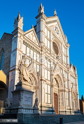 The front of Basilica of Santa Croce in Florence, Italy with the monument to Dante Aligheiri in the foreground,