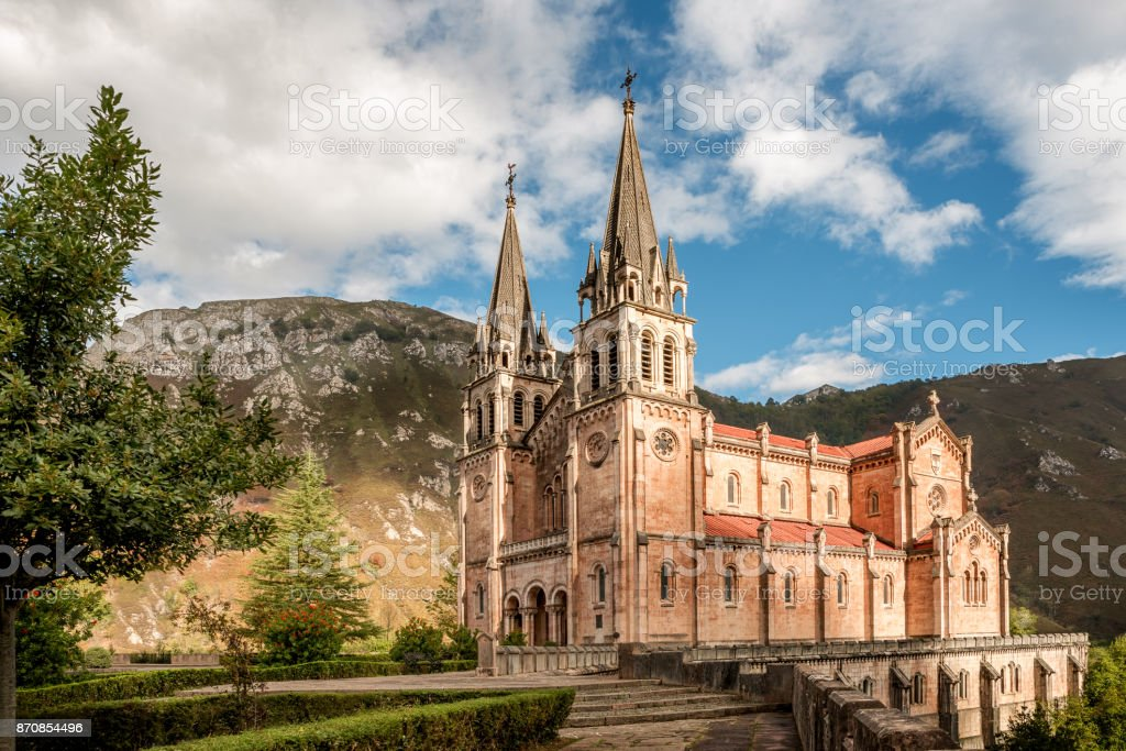 Basilica of Santa Maria la Real de Covadonga, Asturias, Spain, Europe. Beautiful church of touristic travel destination in autumn with a vibrant colorful sky and green natural forest with mountains. stock photo