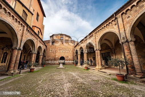Bologna, Emilia-Romagna, Italy, - feb 23, 2020: Bologna, Basilica of Santo Stefano also called the Seven Churches, Basilica of the Sepulcher and the cloister with columns and brick wall. Italy, Europe. Some tourists stroll under the arcades of the ancient cloister