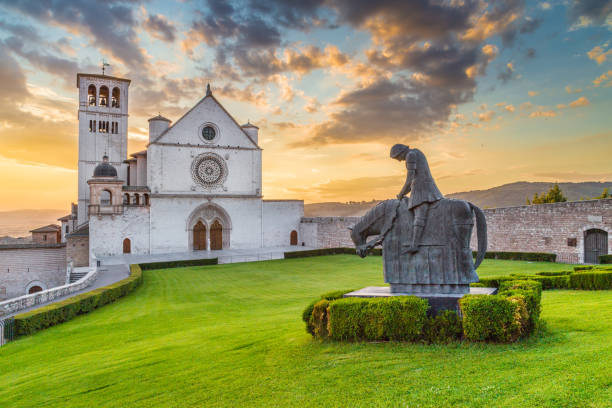 Basilica of St. Francis of Assisi at sunset, Umbria, Italy Classic view of famous Basilica of St. Francis of Assisi (Basilica Papale di San Francesco) with statue in beautiful golden evening light with dramatic clouds in the sky at sunset, Assisi, Umbria, Italy umbria stock pictures, royalty-free photos & images