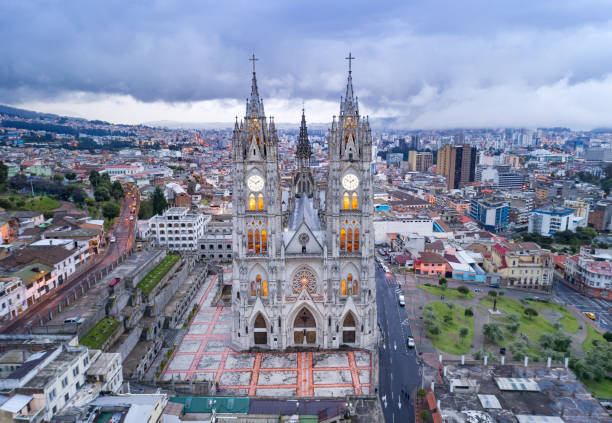 Basílica del Voto Nacional, Quito, Ecuador Aerial perspective of the beautiful Basílica del Voto Nacional at sunset with the typical clouds hanging over Quito, the capital of Ecuador. The city and church lights have just been illuminated. basilica stock pictures, royalty-free photos & images