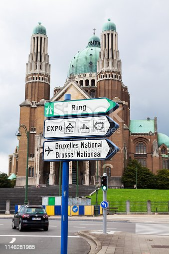 Basilica of the Sacred Heart  and road signs on Keukelberg in Brussels. A car is crossing junction. Cathedral is made in art deco style and is landmark.