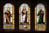 Rome, Italy - May 12, 2018: Basilica del Sacro Cuore. Close up on the stained glass which depicts Jesus Christ having the apostle St. Paul on his left and St. Peter on his right. The artwork was made by Costantino Sereno (Casale Monferrato, 1829 – Torino, 1893).