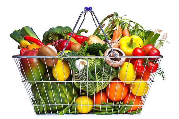 A basket filled with fruits and vegetables Photo of a wire shopping basket full of fresh fruit and vegetables, isolated on a white background. shopping basket stock pictures, royalty-free photos & images