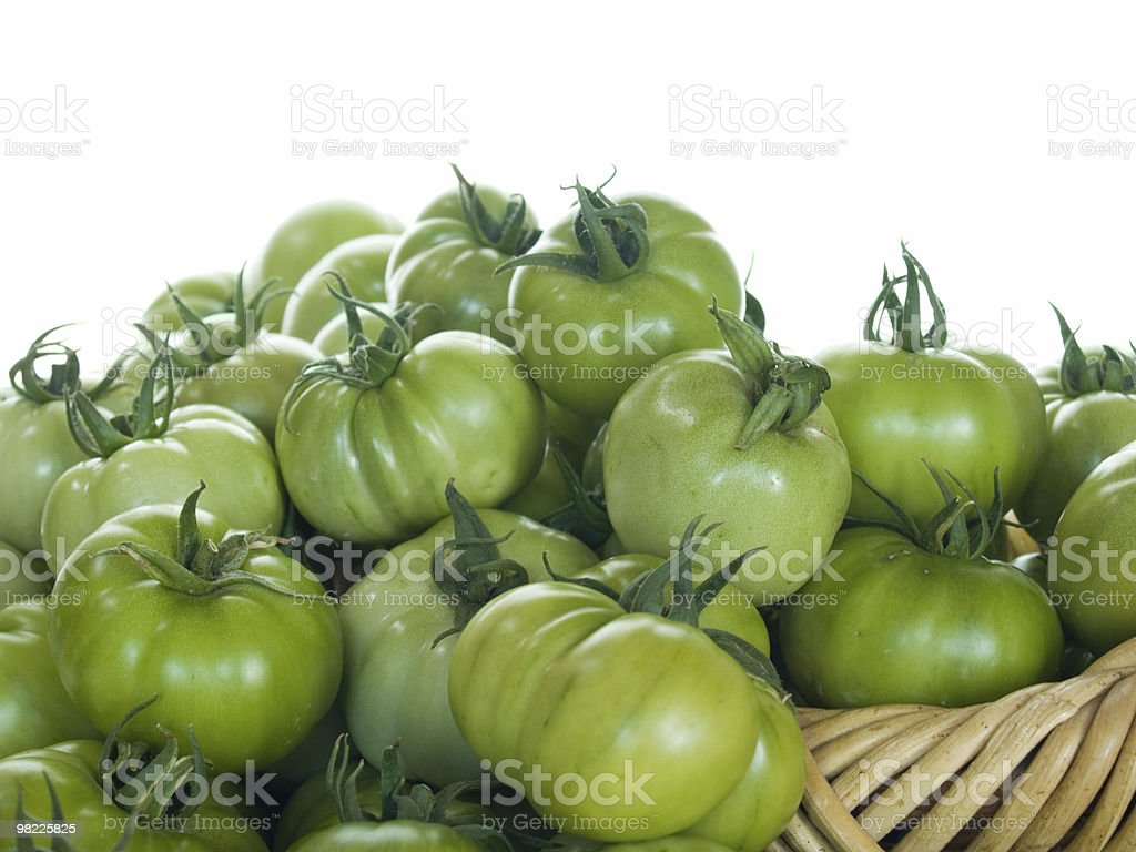 Basket filled with green tomatoes royalty-free stock photo