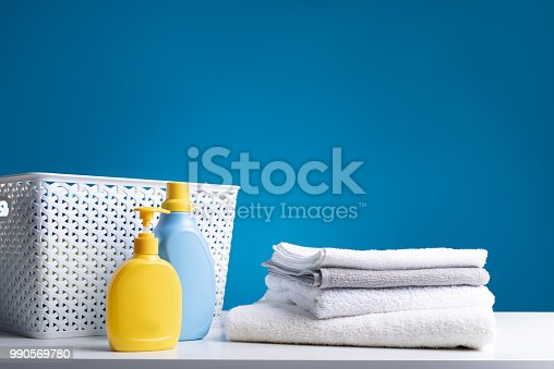 istock Basket for linens and laundry liquids on wooden board 990569780