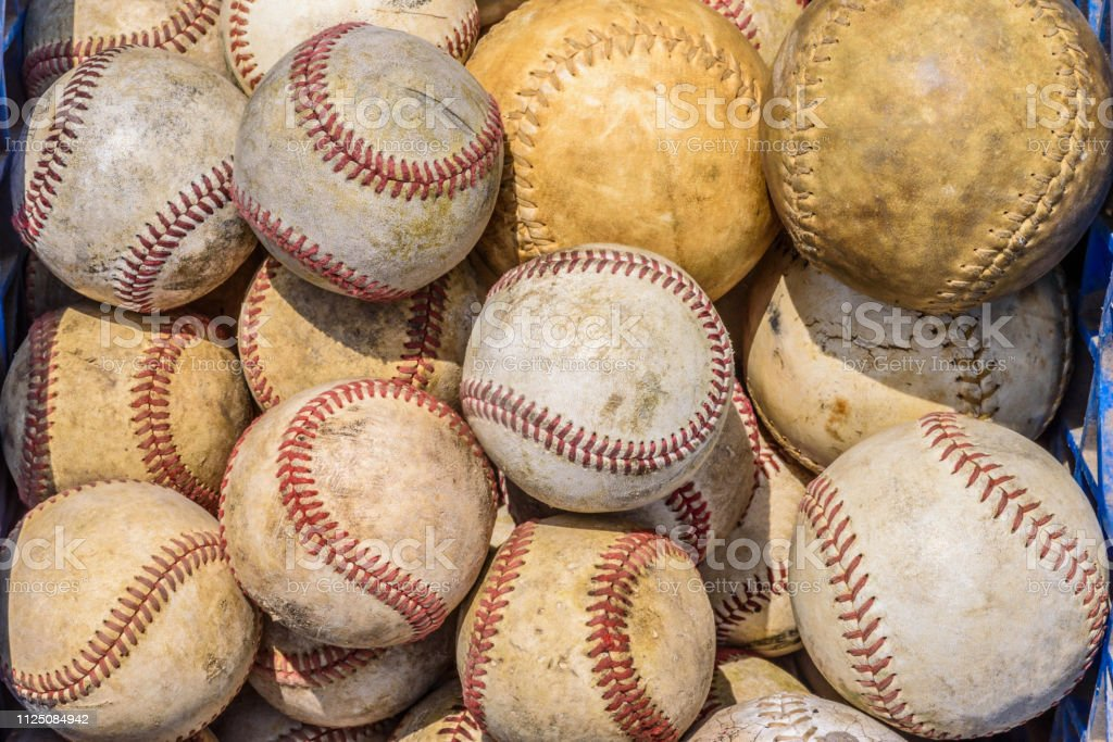 Bucket of old weathered baseballs and softballs for batting practice...