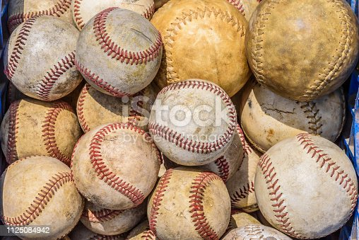 Bucket of old weathered baseballs and softballs for batting practice outdoors in sunlight