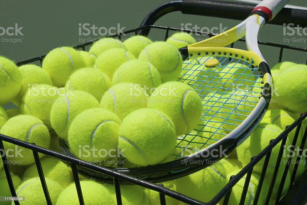 Basket full of tennis balls and a tennis racket royalty-free stock photo