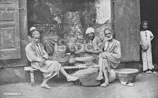Group of men making baskets for sale in Cairo, Egypt. Vintage halftone photo etching circa late 19th century.