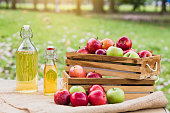 Basket of apples and apple juice in the organic orchard, harvesting and healthy food concept