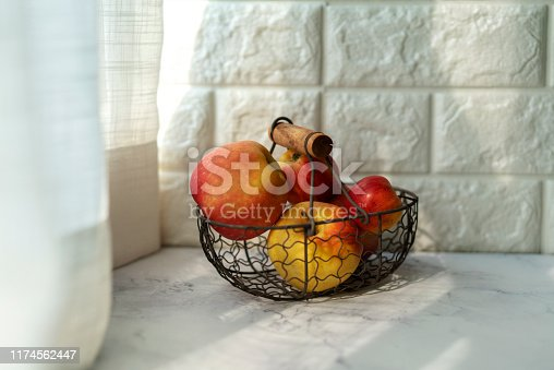 basket of apples on table beside window
