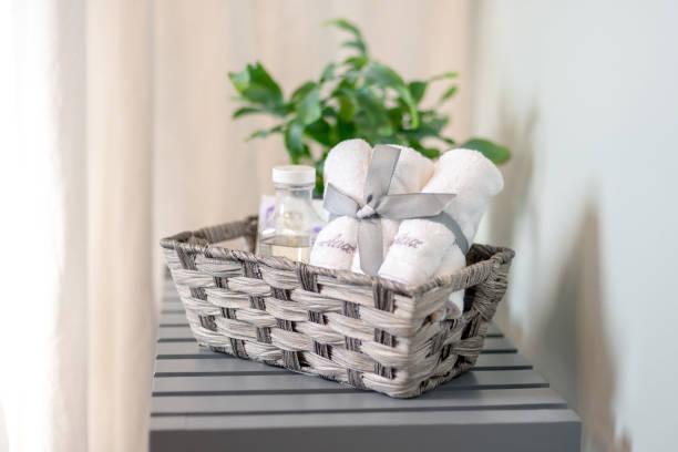 basket of bath products beside the tub - prodotto per l'igiene personale foto e immagini stock