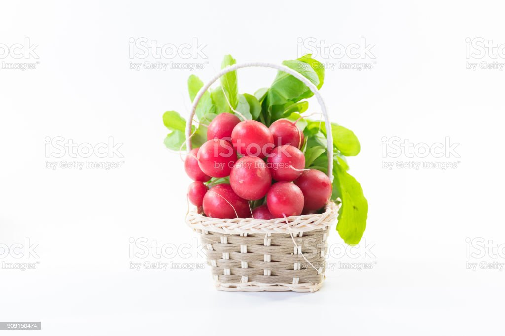 A basket of bunch of fresh small red purple radishes on isolated white background stock photo