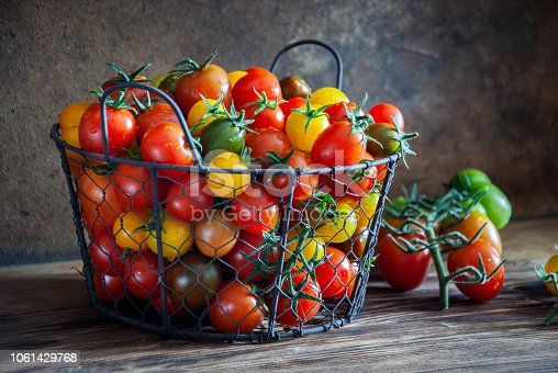 Organic multicolored cherry tomatoes in a metal basket on a wooden background