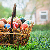 A basket of decorated Easter eggs sitting in the grass outside.