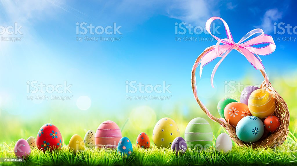 Basket of Easter Eggs On Sunny Meadow stock photo
