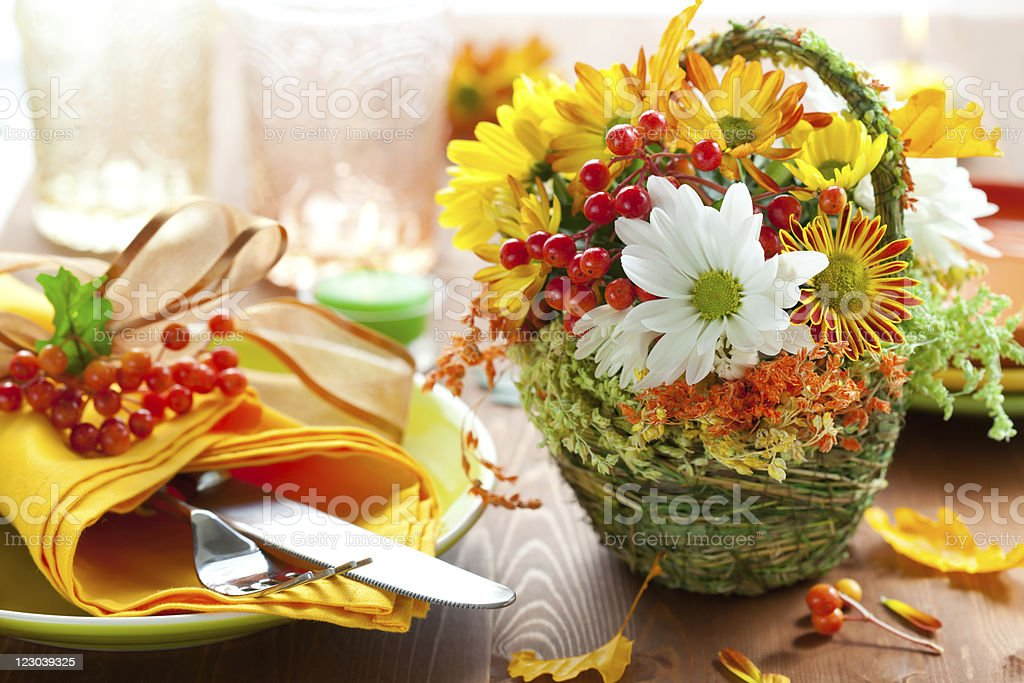 Basket of flowers and table setting with autumn theme royalty-free stock photo