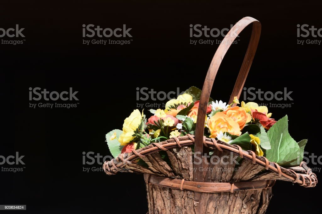 A basket of flowers on a black background