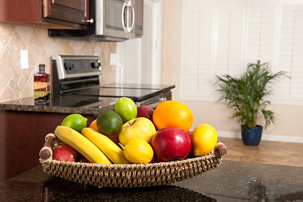 korb mit frischem obst in der modernen küche - obstkorb stock-fotos und bilder