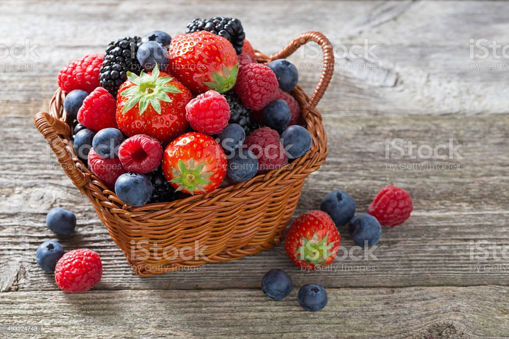 basket of fresh seasonal berries on wooden table, top view stock photo
