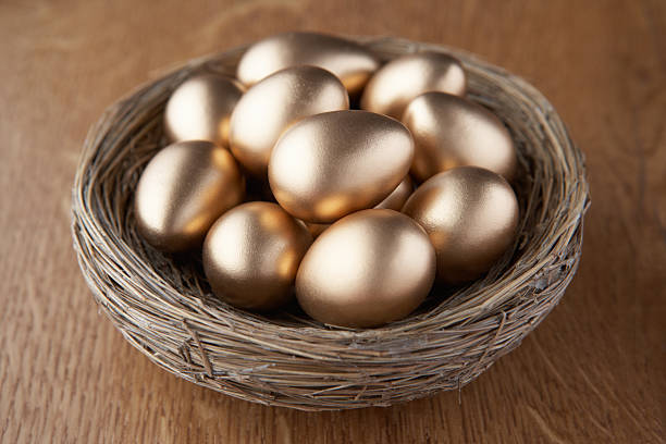 Basket of golden eggs A basket of golden eggs on wooden table nest egg stock pictures, royalty-free photos & images