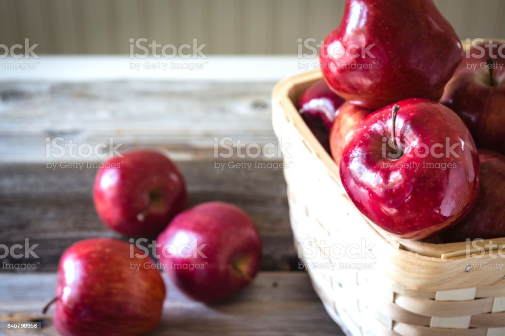 basket of red apples on wood background. stock photo