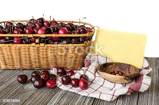 istock Basket of red sweet cherries and a card for text message 976316354