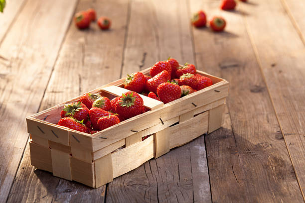 Basket of strawberries Basket of strawberries on a sunny wooden table fruit carton stock pictures, royalty-free photos & images