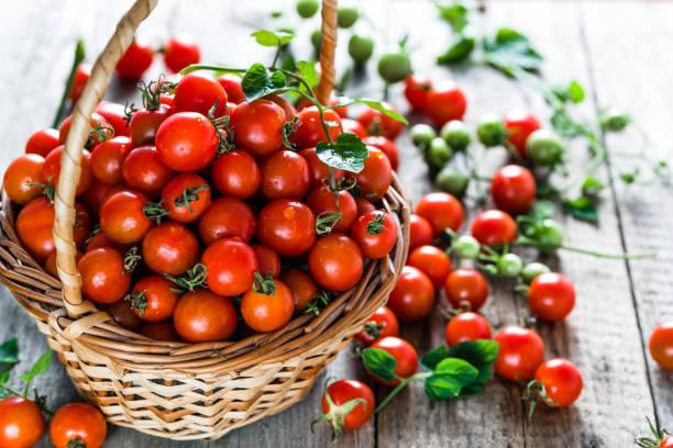 korg av tomater uppmanade trä bakgrund, färska körsbär tomat producera på lokala marknaden - körsbärstomat bildbanksfoton och bilder