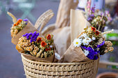 Basket with beautiful autumn bouquet of dry flowers, wrapped in the paper