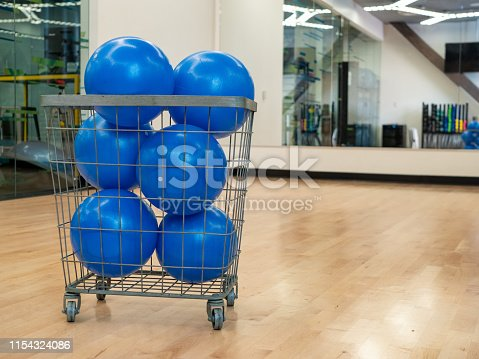 istock Basket with blue core exercise balls in an exercise studio with mirror 1154324086