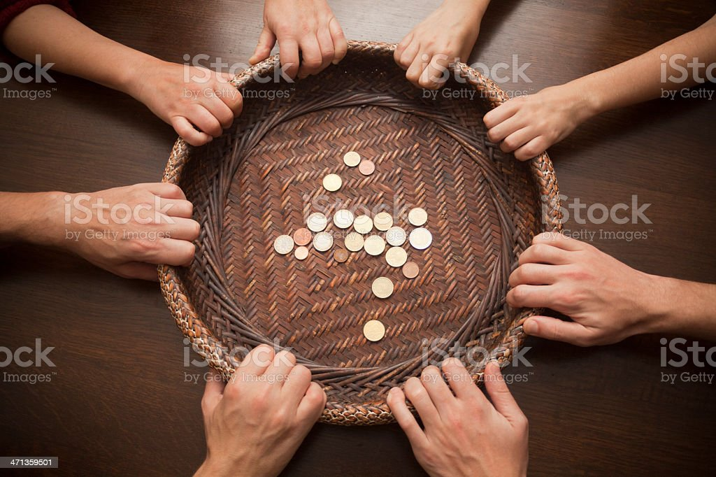 Basket with coins and hands pulling it stock photo