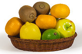Basket with different tropical fruits isolated on white