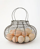Photograph of a basket full of eggs on white background.