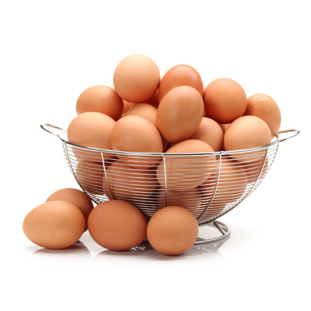 Basket with eggs in front of white background stock photo