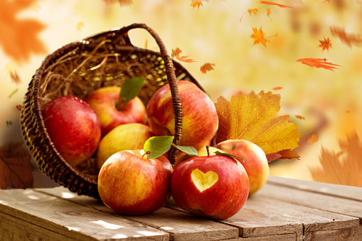 istock Basket with fresh apples on wooden table in autumn 1148620760