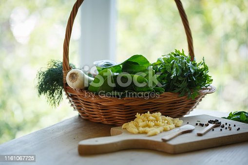 Flat lay of wooden basket with fresh herbs like chard, parsley, dill and leak next to a cutting board with pasta and wooden spoons with salt and pepper.