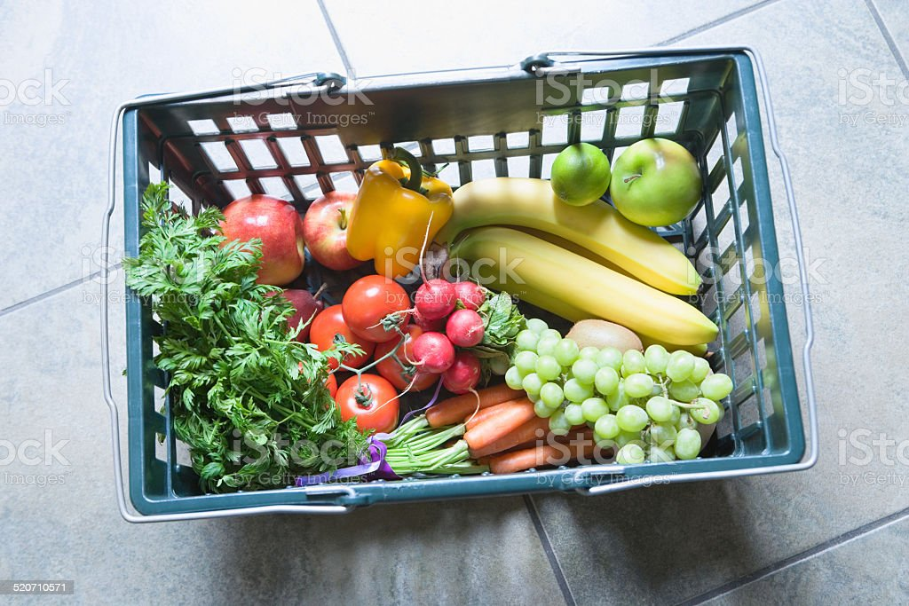 Basket with fruits and vegetables on floor, overhead view stock photo