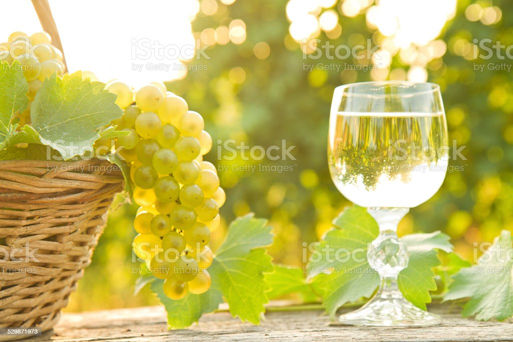 Basket with grapes next to a glass of wine stock photo