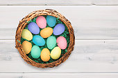 Basket on white washed wood background filled with colored eggs