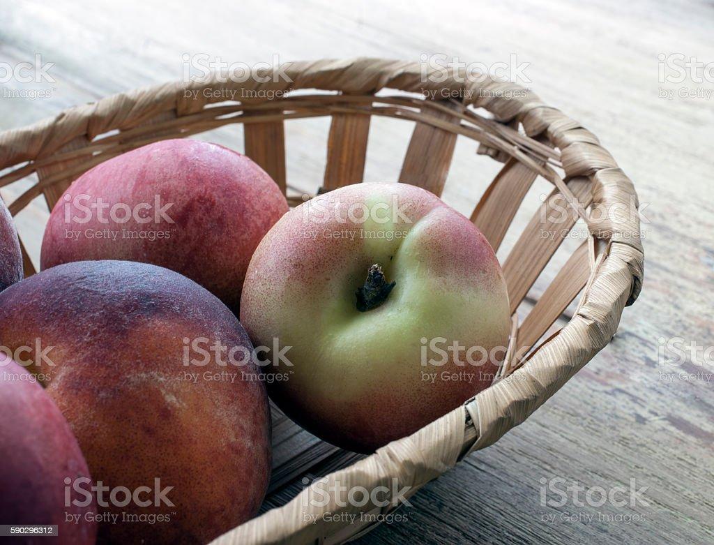 Basket with peaches on a table Стоковые фото Стоковая фотография