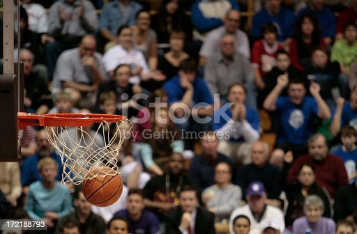 Basketball fans sitting on the blechers show emotion as a basketball falls through the basket and net to score.