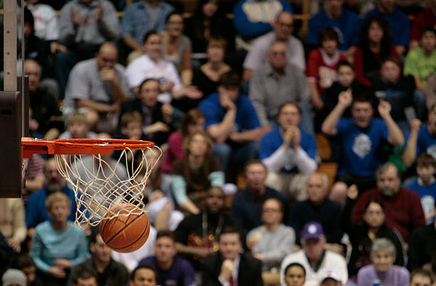 basketball ball and backboard with fans in the background. - basketball ball stock photos and pictures