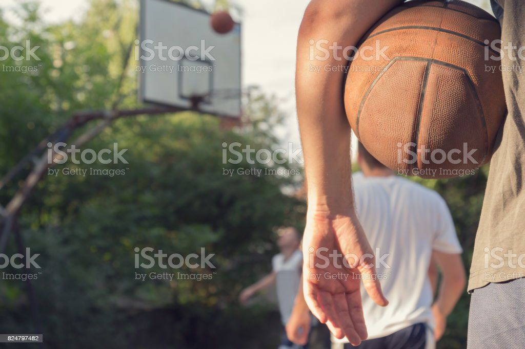 Basketball ball and player with defocused sports playground.