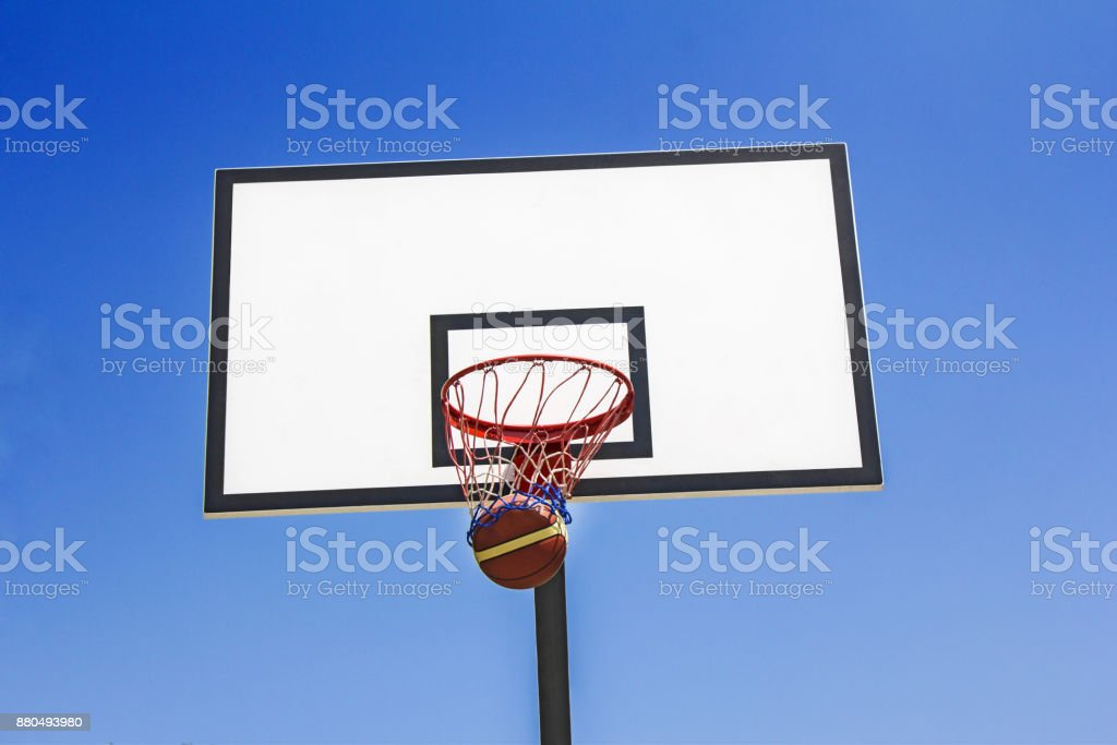 Basketball ball hit the basket in the blue sky background stock photo