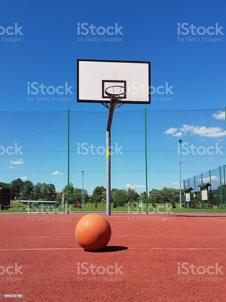 A basketball ball lies in front of a basketball ring at the stadium. royalty-free stock photo