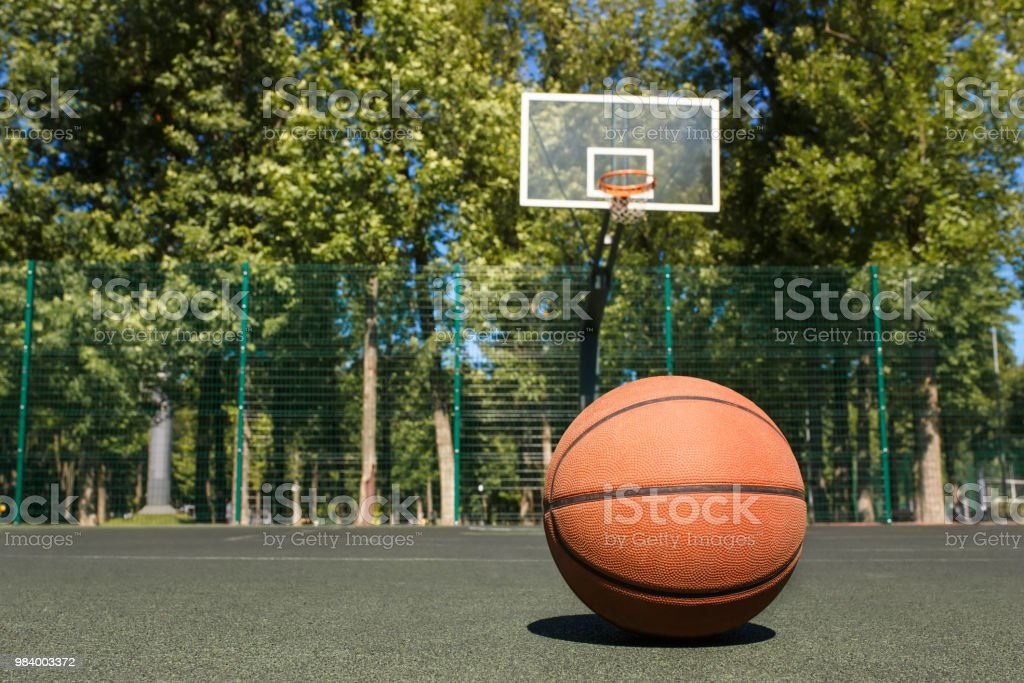 basketball ball on the outdoors court with hoop on the background
